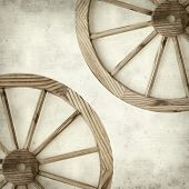 image of wagon wheel  - textured old paper background with old wagon wheel - JPG