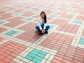 Photo of woman sitting on the paving slab