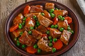 stock photo of stew  - beef stew with peas and carrots on a plate - JPG