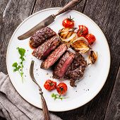 picture of ribeye steak  - Sliced medium rare grilled Beef steak Ribeye with grilled onions and cherry tomatoes on plate on wooden background - JPG