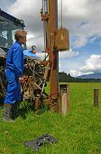 stock photo of groundwater  - A man uses a fence post driver to generate sound waves through the ground in an electro-seismic survey for well water