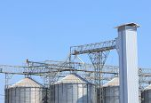 stock photo of silo  - exterior structure of new agriculture silo building against blue sky - JPG
