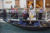 Gondoliers helping tourist to board the gondola ride at Grand Canal at The Venetian Resort