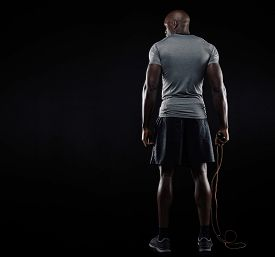 image of roping  - Rear view of muscular man standing with jumping rope on black background - JPG
