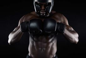stock photo of boxers  - Portrait of young african male boxer preparing for competition against black background - JPG