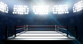 stock photo of boxing  - An boxing ring surrounded by ropes spotlit by floodlights in an arena setting at night - JPG