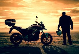 stock photo of biker  - Biker standing with its motorbike on a misty sunset - JPG