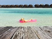 stock photo of mattress  - Woman relaxing on inflatable mattress at the beach - JPG