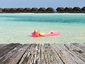 foto of mattress  - Woman relaxing on inflatable mattress at the beach - JPG