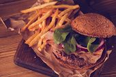 stock photo of burger  - Burger and french fries with meat and vegetables close up on a vintage style on wooden background - JPG