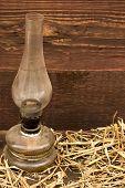picture of kerosene lamp  - Kerosene lamp with hay on rustic wooden background - JPG