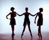 stock photo of shoot out  - Composition from silhouettes of three young dancers in ballet poses on a gray background - JPG