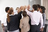 stock photo of joining hands  - Group Of Businesspeople Joining Hands In Circle At Company Seminar - JPG