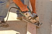 foto of worm  - Building contractor worker using hand held worm drive circular saw to cut boards on a new home construciton project - JPG