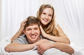 picture of laying-in-bed  - Happy smiling couple laying laughing in bed on light window background - JPG