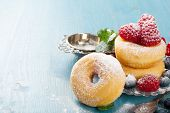 stock photo of donut  - Morning breakfast with mini donuts and berries on plate under powdered sugar on blue wooden background - JPG