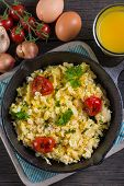 pic of scrambled eggs  - scrambled egg with grilled tomato in vintage iron pan from above - JPG