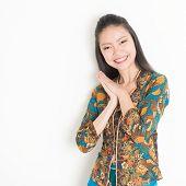stock photo of southeast  - Portrait of happy Southeast Asian woman in batik dress on plain background - JPG