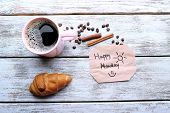 stock photo of monday  - Cup of coffee with fresh croissant and Happy Monday massage on wooden table - JPG