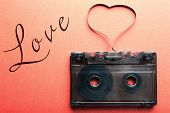 image of magnetic tape  - Audio cassette with magnetic tape in shape of heart on red background - JPG