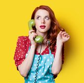 pic of redhead  - Surprised redhead girl in red polka dot dress and blue apron with green dial phone on yellow background - JPG