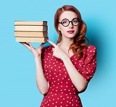 image of redhead  - Young redhead teacher in red polka dot dress with books on blue background - JPG