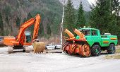 image of mountain chain  - An excavator with a rotating house platform on tracks and a snow removal vehicle with snow chains in Friuli - JPG