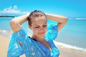 picture of young woman posing the camera  - Young attractive woman posing and smiling at camera in front of sea shore - JPG