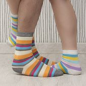 stock photo of stocking-foot  - feet of a beautiful couple with striped socks - JPG