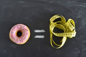 foto of addicted  - donut and tailor measure tape on blackboard representing sugar sweet abuse and addiction equal body overweight and unhealthy nutrition in conceptual image - JPG