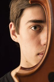 image of cello  - A young man holding a cello peeking from behind it - JPG