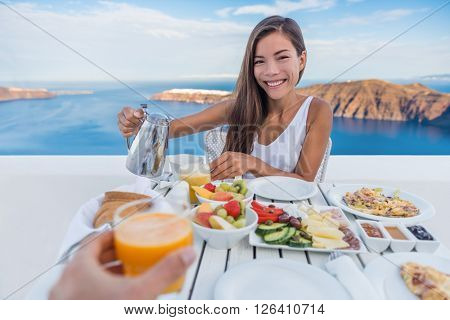 Couple eating breakfast. Smiling tourist woman drinking coffee and man drinking orange juice on terr