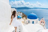Santorini travel tourist woman on vacation in Oia walking on stairs. Person in white dress visiting  poster