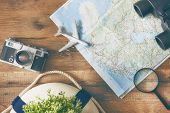 Go on an adventure! The map and the camera on a wooden table. Top view. poster