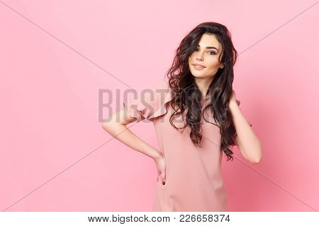poster of Beautiful Fashionable Girl With Long Curly Hair In A Pink Dress In The Studio On A Pink Background.