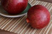A Pair Of Juicy Red Pomegranate Lying On A Wooden Table On A Bamboo Napkin. One Pomegranate Fruit Li poster