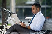 Serious Busy Man Searching Job In Newspaper While Sitting On Bench In Park. Concentrated Modern Male poster