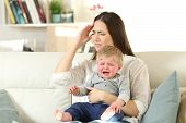 Mother Suffering And Baby Crying Desperately Sitting On A Couch In The Living Room At Home poster
