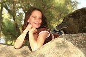 Happy Young Girl Outdoors On A Rock poster