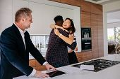 Excited Couple Hugging With Real Estate Agent In Kitchen Of New Home. Happy New Property Owners With poster
