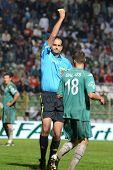 KAPOSVAR, HUNGARY - JULY 30: Adam Nemeth (referee) presents yellow card at a Hungarian National Championship soccer game - Kaposvar (green) vs Videoton (white) on July 30, 2011 in Kaposvar, Hungary.