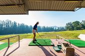Young Woman Practices Her Golf Swing On Driving Range, View From Behind,young Girls Practicing Drivi poster