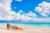 Beach travel vacation paradise sexy bikini woman lying down on sand relaxing sun tanning in tropical poster