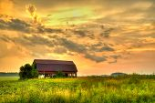 American Midwest Barn Landscape. Sunset Over A Farm Field With A Traditional Red Barn At The Horizon poster