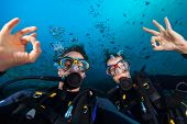 Couple of scuba divers showing ok sign, portrait photography. Underwater sports and activities poster