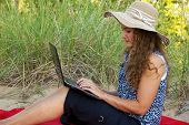 stock photo of black curly hair  - Young woman on laptop on a blanket - JPG