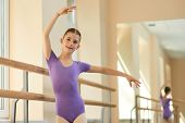 Girl Training At Professional Ballet School. Young Beautiful Ballerina Doing Exercise At Ballet Clas poster