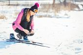 Woman cross country skier putting on ski on the slope  poster