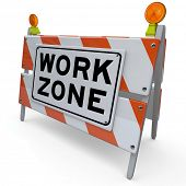 An orange and white construction barricade sign blocking an area that is a designated work zone wher