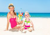 Mother And Daughter On Seashore With Colorful Windmill Toy poster